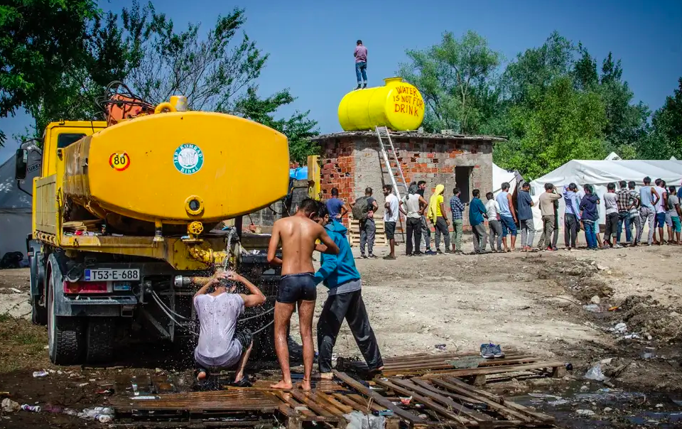 Residents of the camp wait in line for food distributed from Bihać Red Cross, while men wash themselves at the back of a water truck. ( Thom Davies )