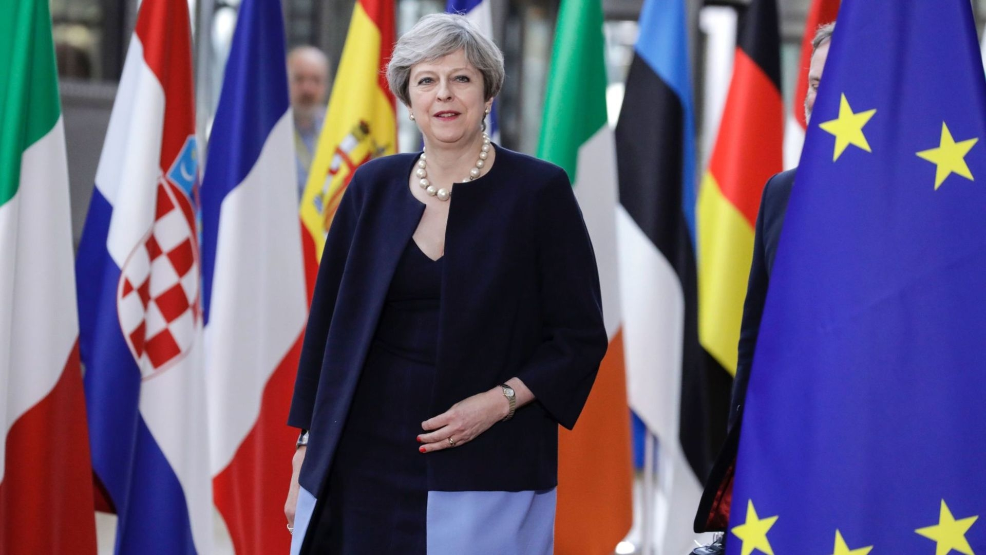 Theresa May made the offer at an EU summit in Brussels to let EU citizens remain in the UK.